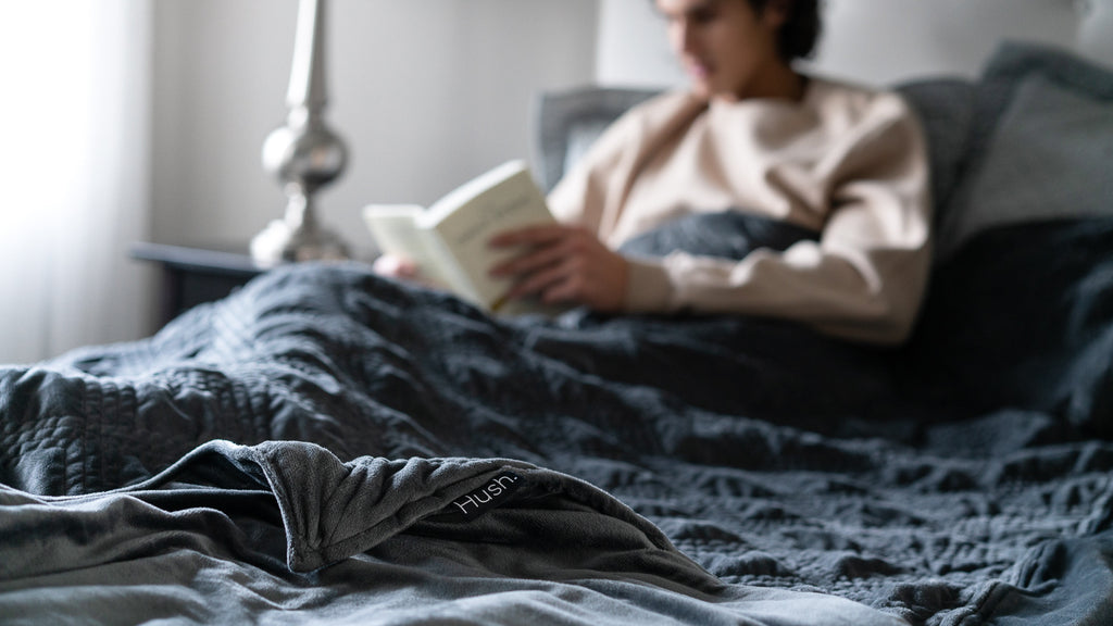 man reading under weighted blanket