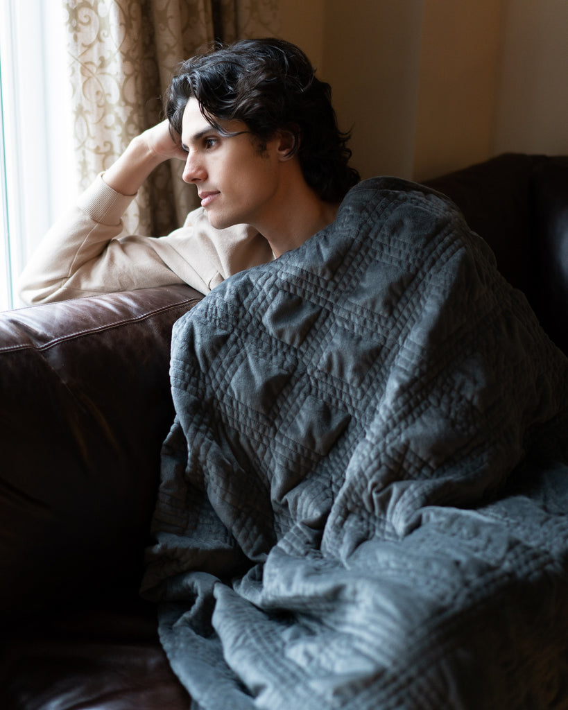 Man staring out the window while covered in a blanket