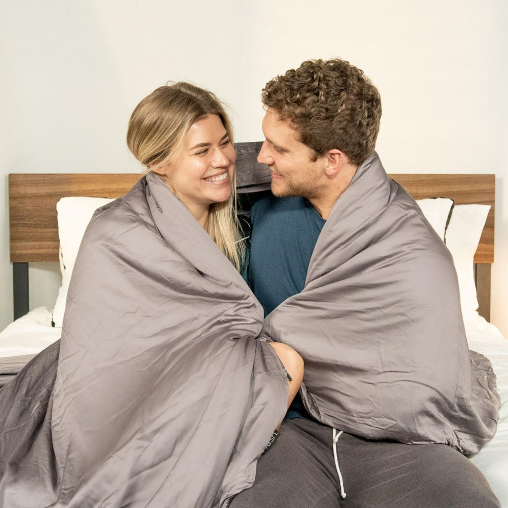 Smiling couple looking at each other with a blanket over their shoulders