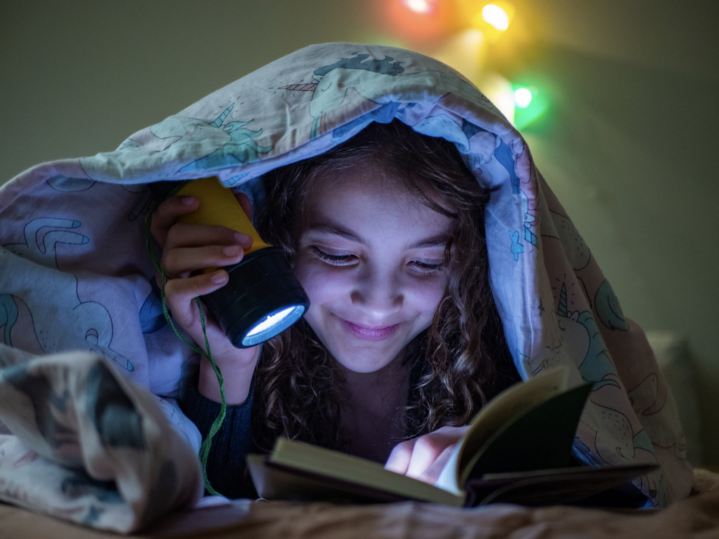 weighted blanket for ADHD: Girl reading a book in the dark using a flashlight while covered with a blanket