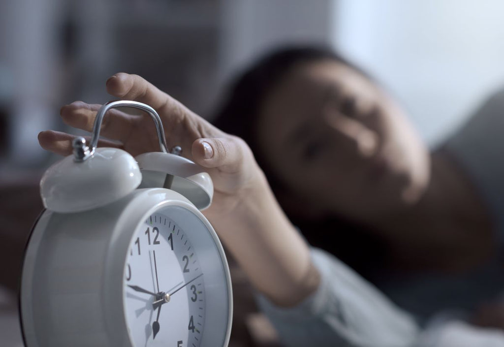 How long does it take to fall asleep: Woman turning off an alarm clock