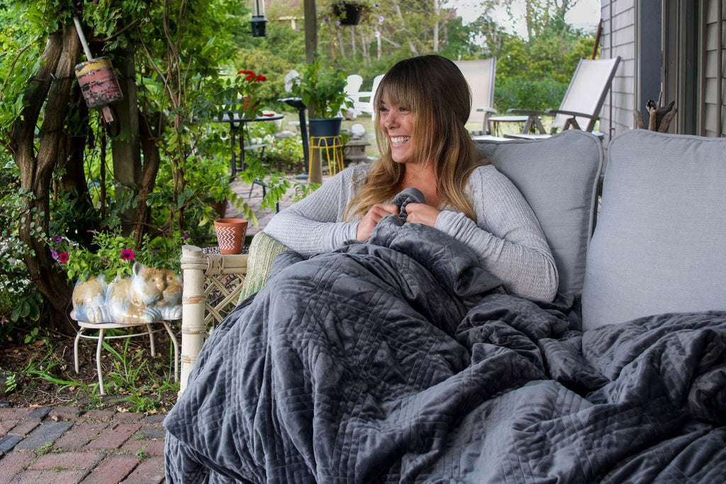 How to wash a weighted blanket: Woman wearing a blanket in a backyard