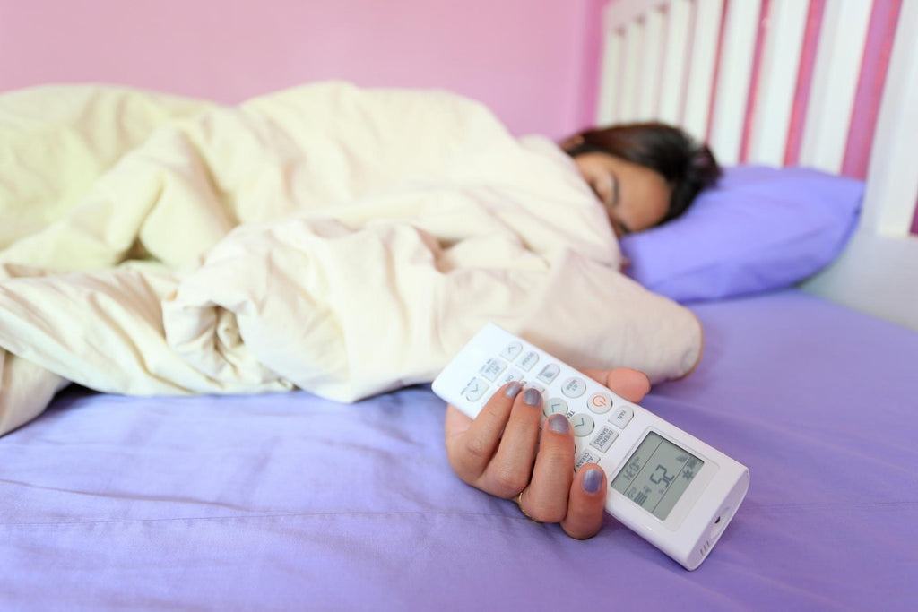 how to stay cool at night: Woman holding the air conditioner remote while sleeping in bed