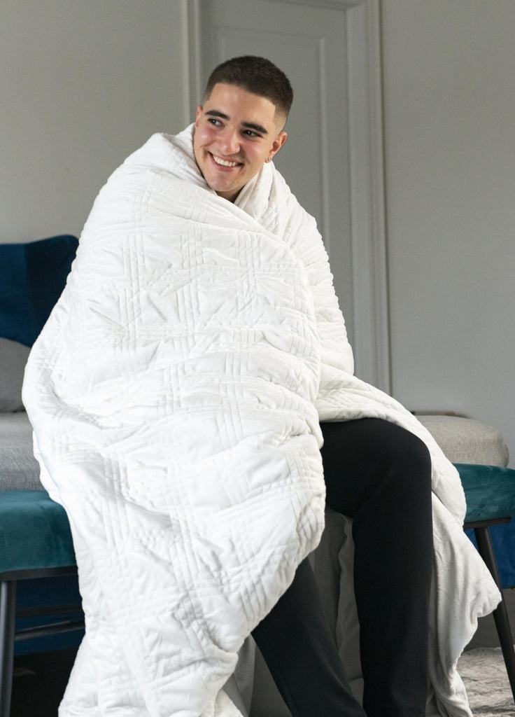 how to calm down: Smiling man sitting at the foot of his bed with a blanket wrapped around his shoulders