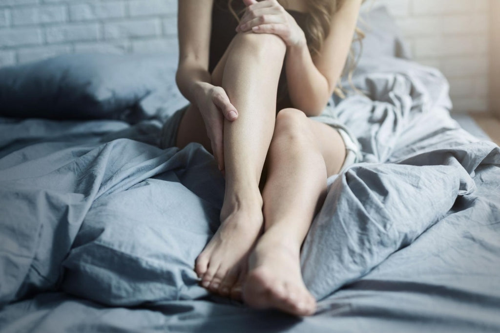 weighted blanket for restless legs: Woman massaging her leg while sitting in bed