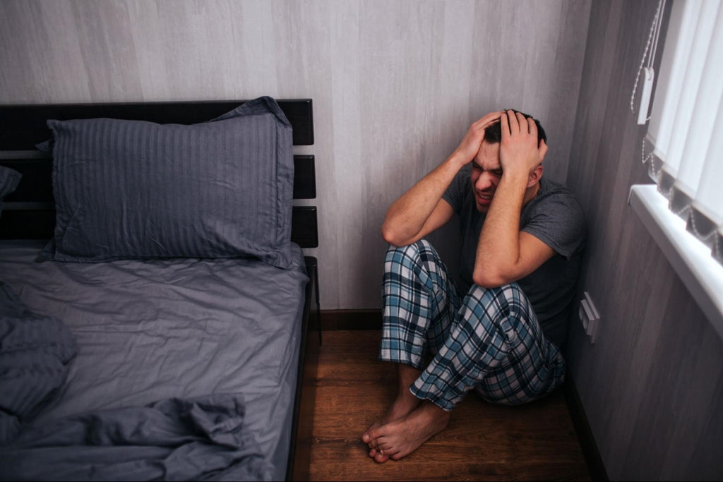 panic attacks at night: Distressed man sitting in a corner of his bedroom
