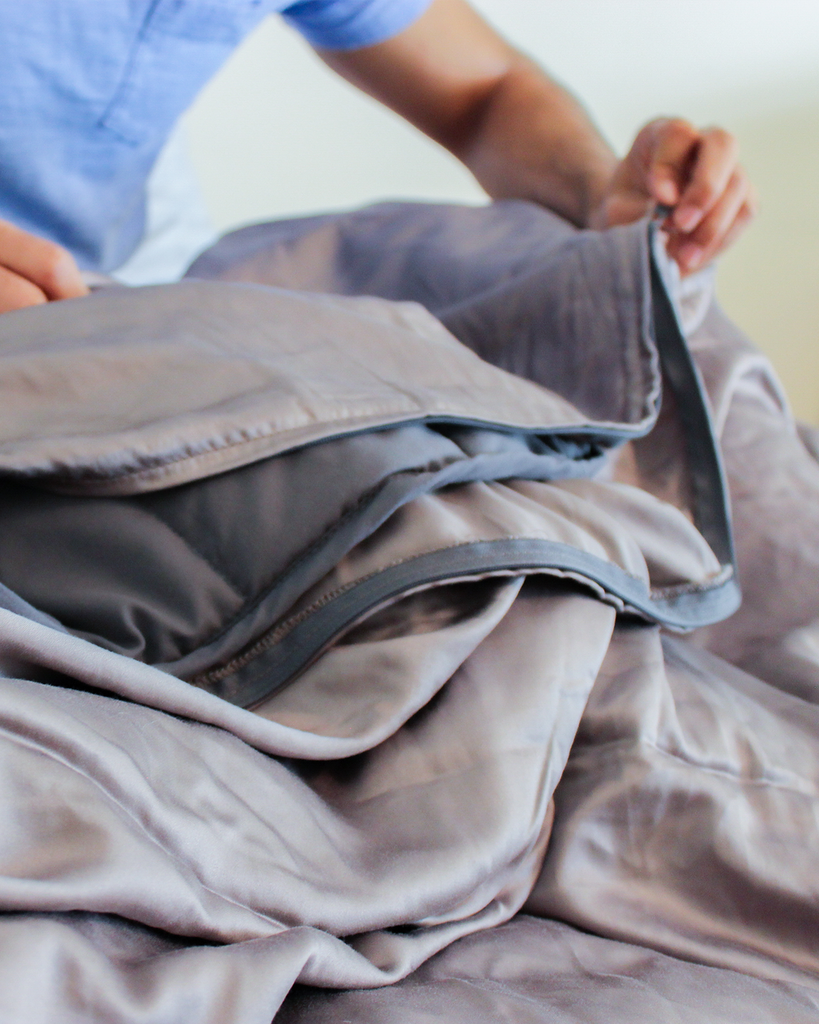 cooling weighted blanket: man folding a blanket
