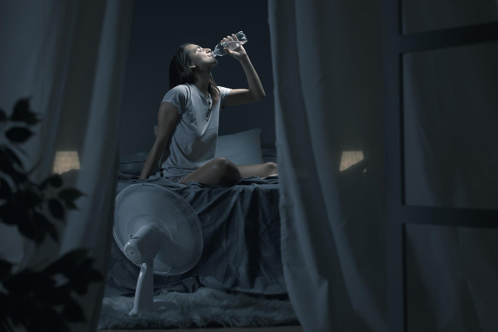 how to stay cool at night: Woman drinking water while sitting on a bed