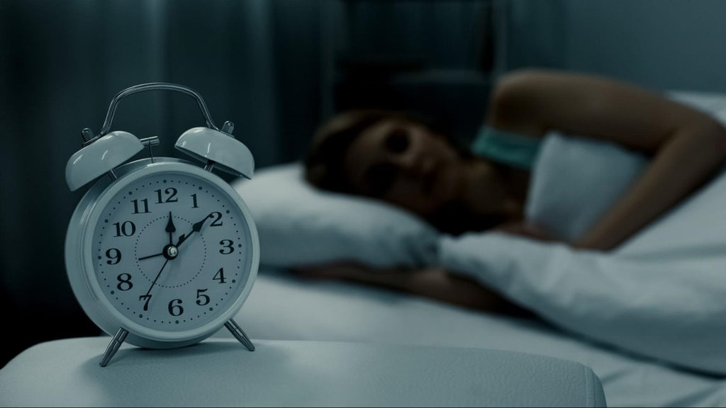 how to make yourself tired: Woman sleeping with an alarm clock on her side table