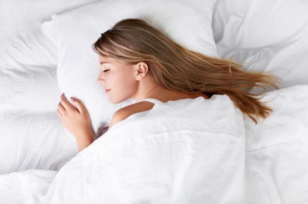 cooling bed sheets: Woman sleeping in bed with a blanket