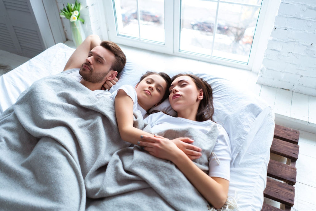 types of blankets: Family of three sleeping in bed