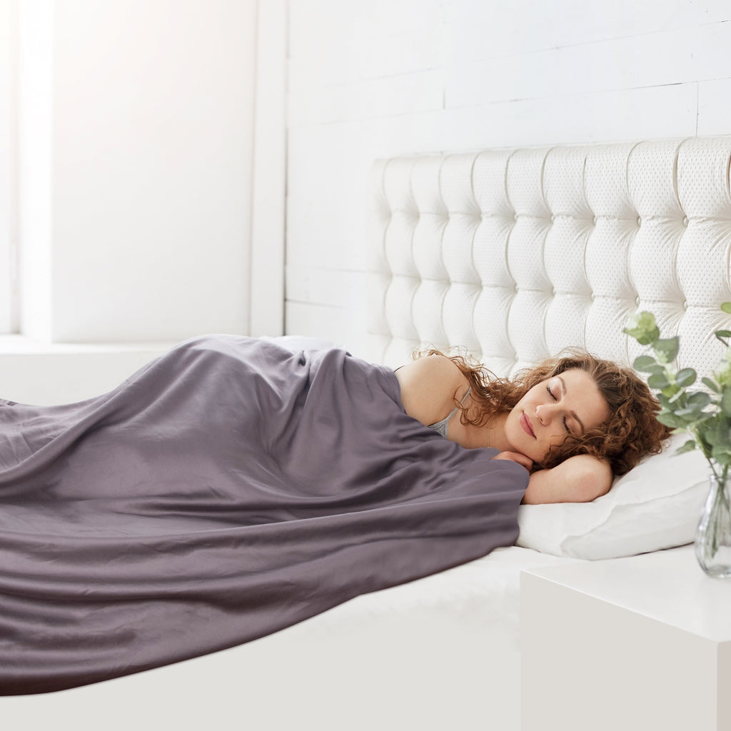 Woman sleeping in bed with a blanket