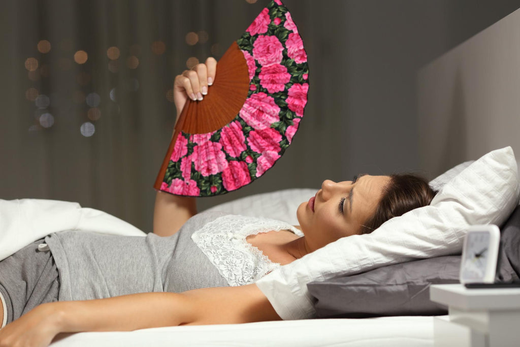 how to stay cool at night: Woman lying in bed while fanning herself