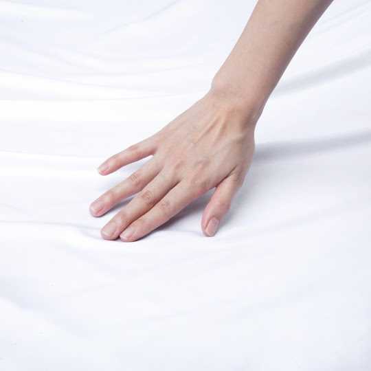 Woman's hand touching a white bed sheet