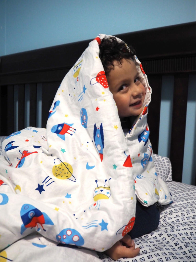how to choose a weighted blanket: Smiling child looking at the camera while wrapped in a blanket