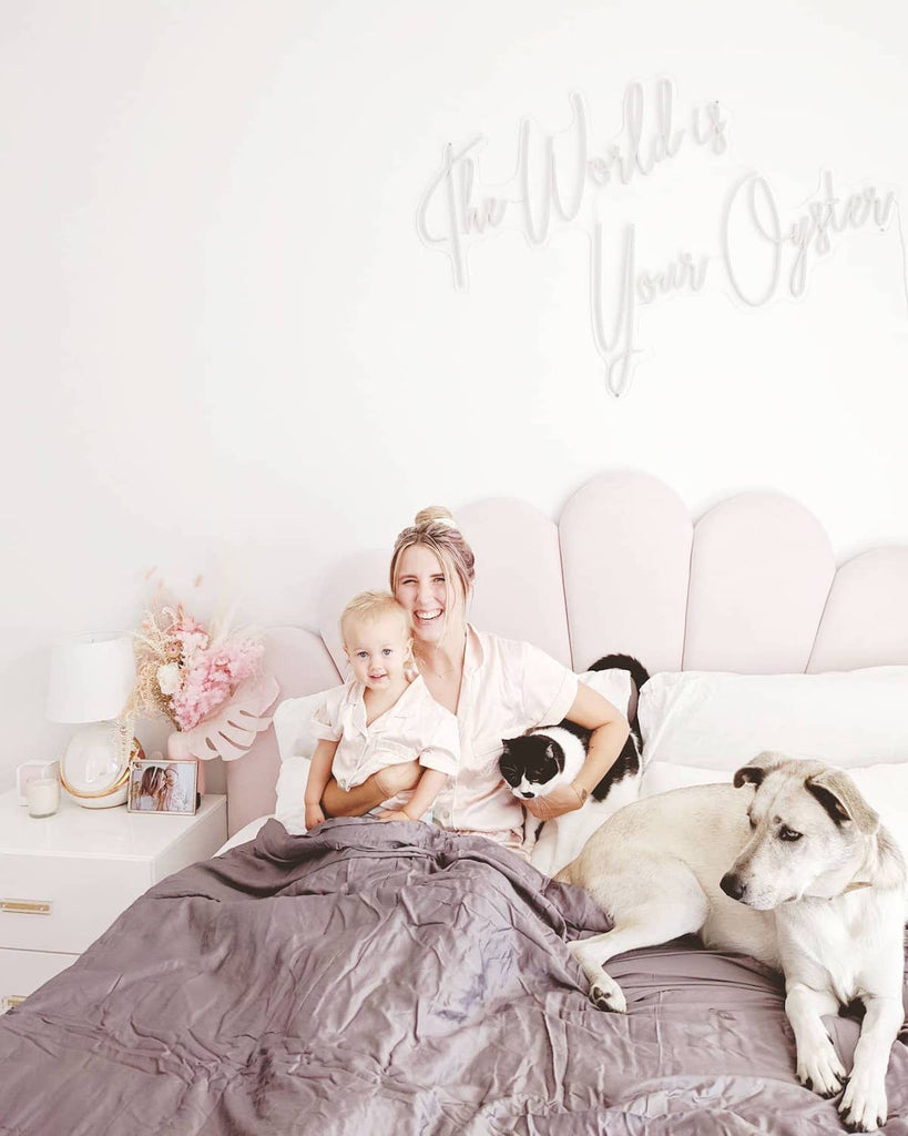 cooling weighted blanket: mom in bed with her kid, cat and dog