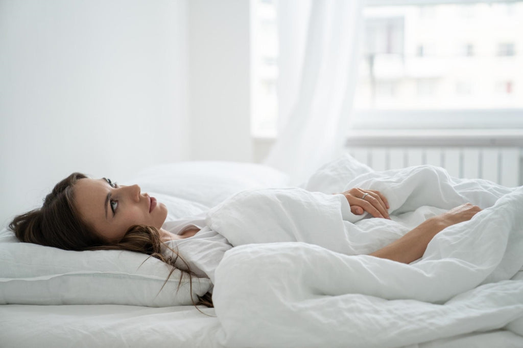 Woman staring up at the ceiling while lying in bed