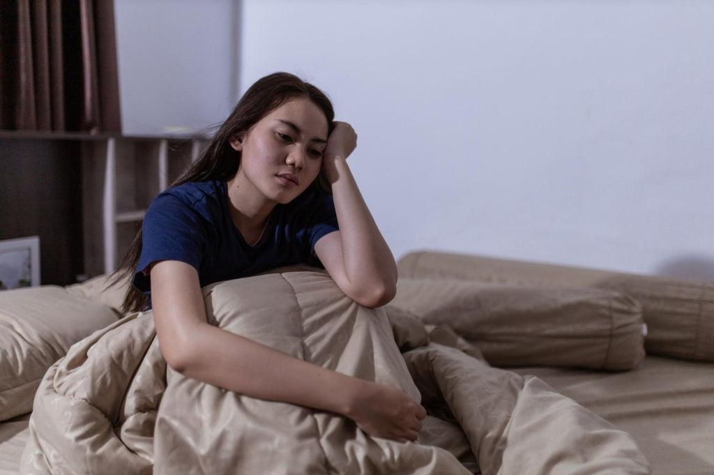 panic attacks at night: Woman having trouble sleeping while sitting in bed