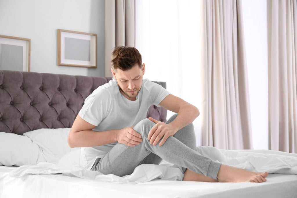 weighted blanket for restless legs: Man massaging his knee while sitting in bed