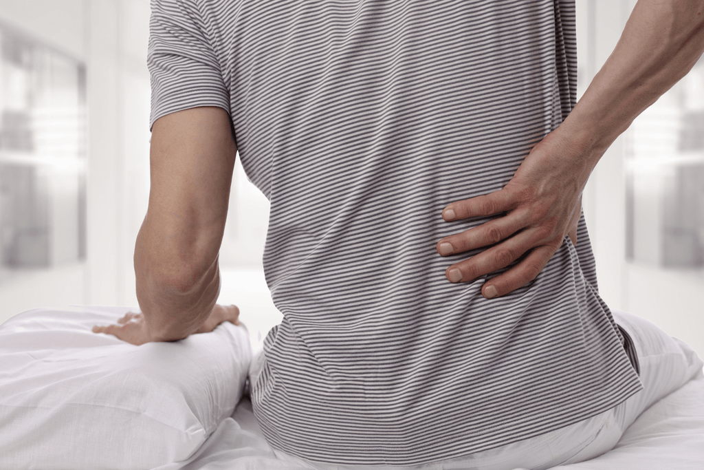 stomach sleeper: Man in pain, holding his back while sitting in bed