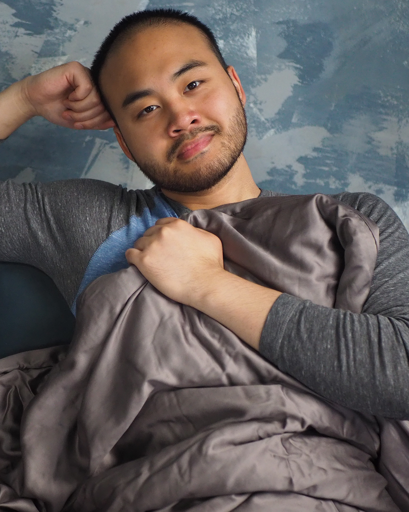 Smiling man looking straight ahead while sitting in bed with a weighted blanket