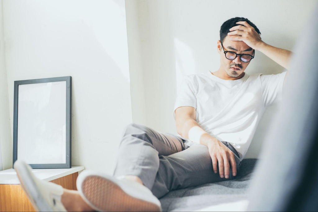 how to manage anxiety without medication: Anxious man holding his head in his hand while sitting on the bed