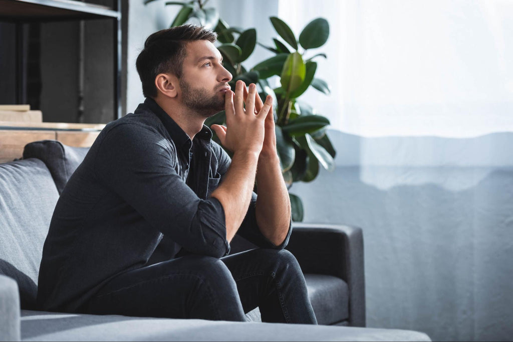 how to manage anxiety without medication: Man looking deep in thought while sitting on a couch