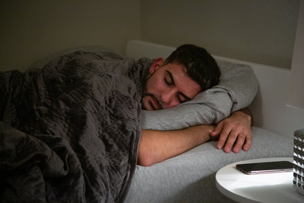 how to sleep when stressed: Man sleeping in bed with a weighted blanket