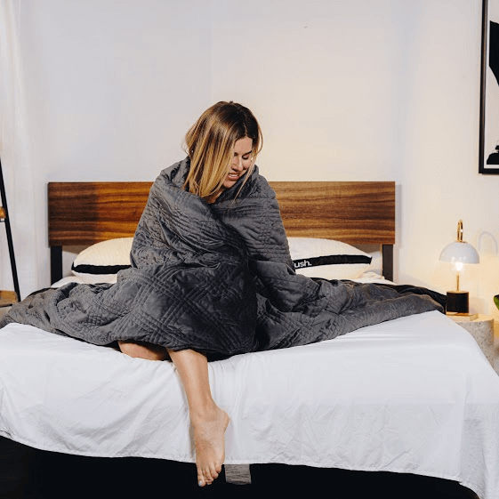 Smiling woman sitting in bed with a weighted blanket wrapped around her