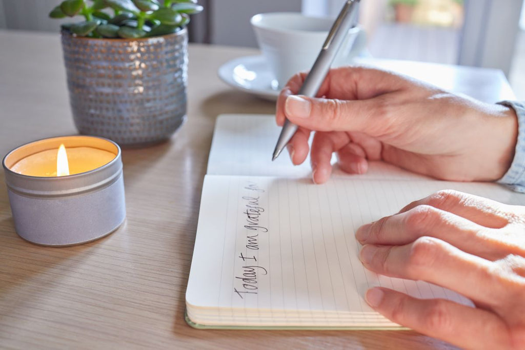 stress relief gifts: woman using a gratitude journal