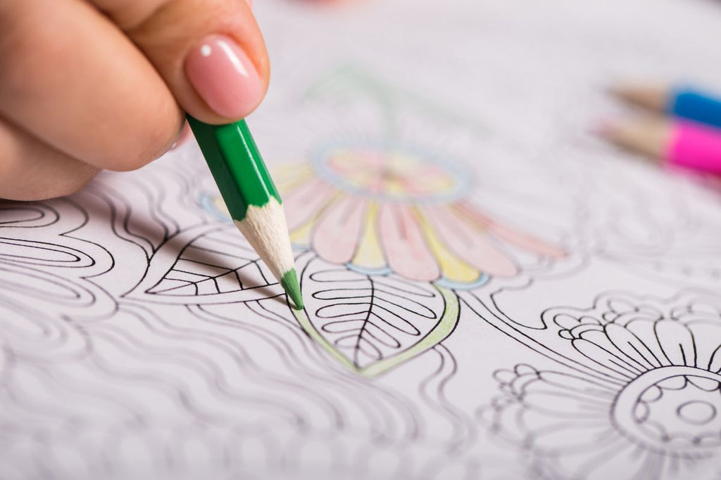 stress relief gifts: person using an adult coloring book