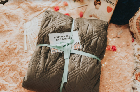 Weighted blanket wrapped as a gift on top of a beige carpet