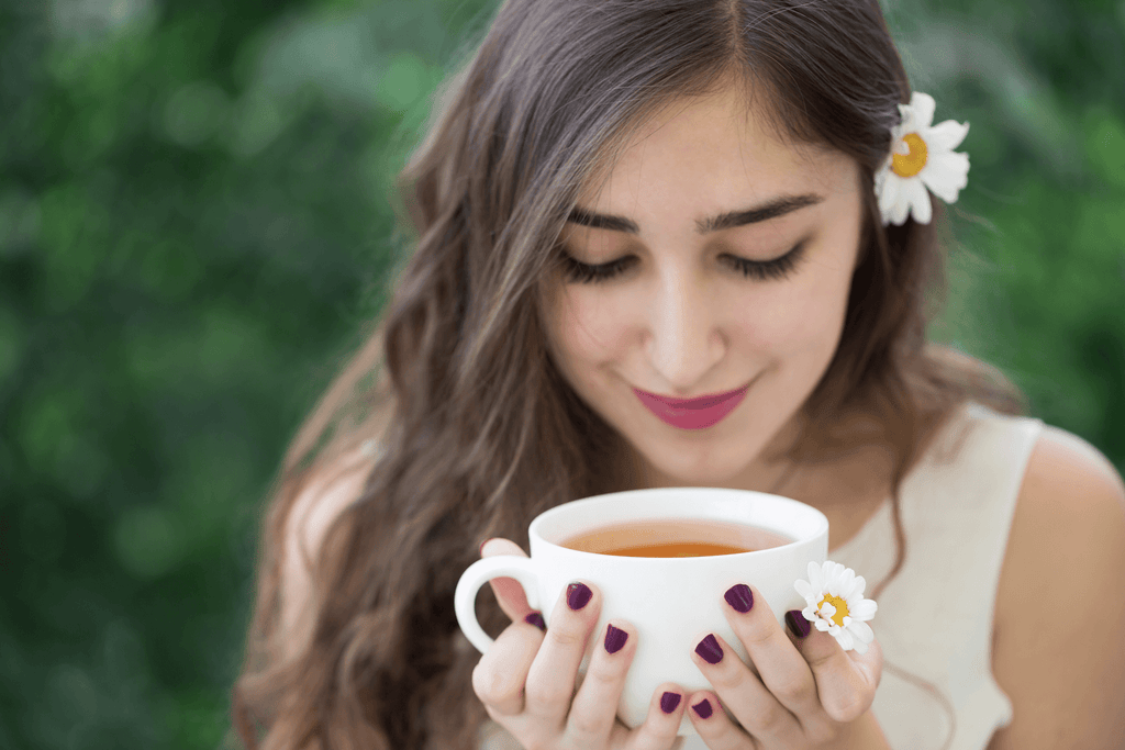 how to fall asleep in 10 seconds:  Smiling woman holding a cup of tea while looking down at it