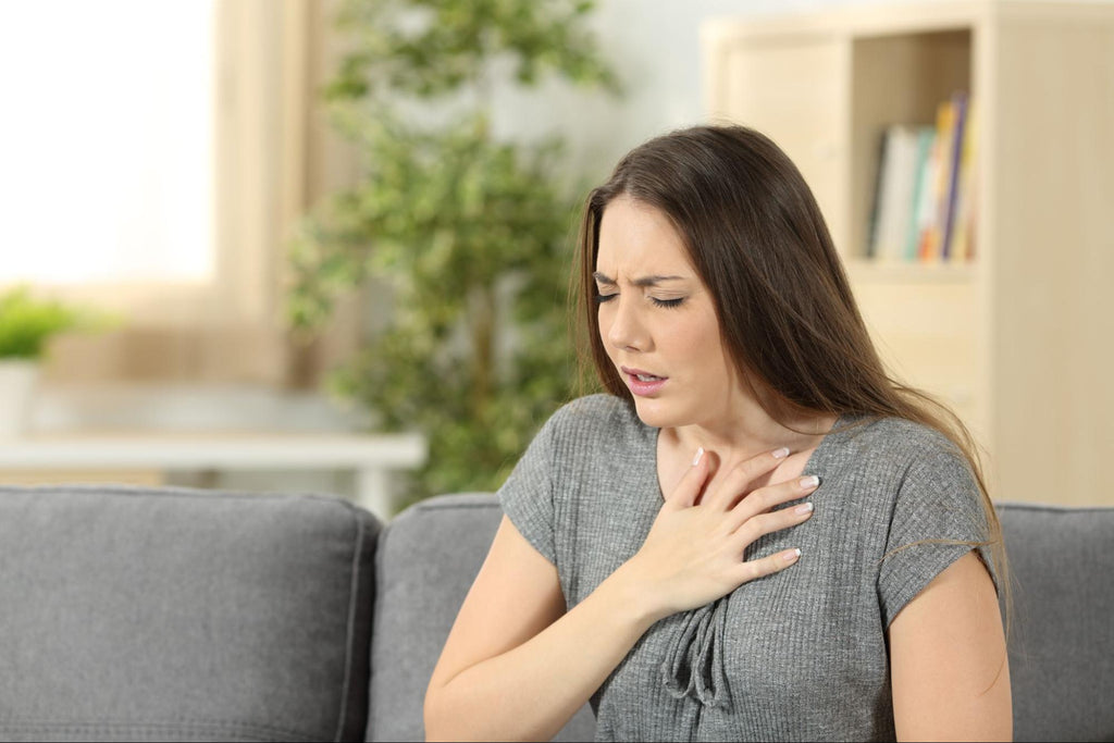 how to manage anxiety without medication: Woman in pain, holding her chest with her eyes closed