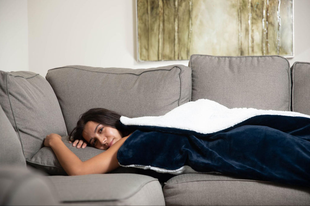 Woman lying on the couch with a weighted blanket