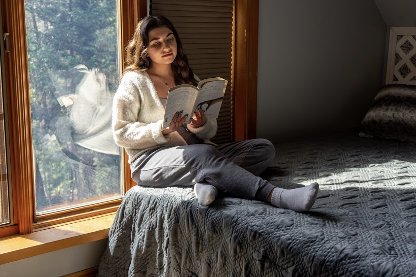 how to relax after work: Woman reading a book while sitting in bed and leaning against the window pane