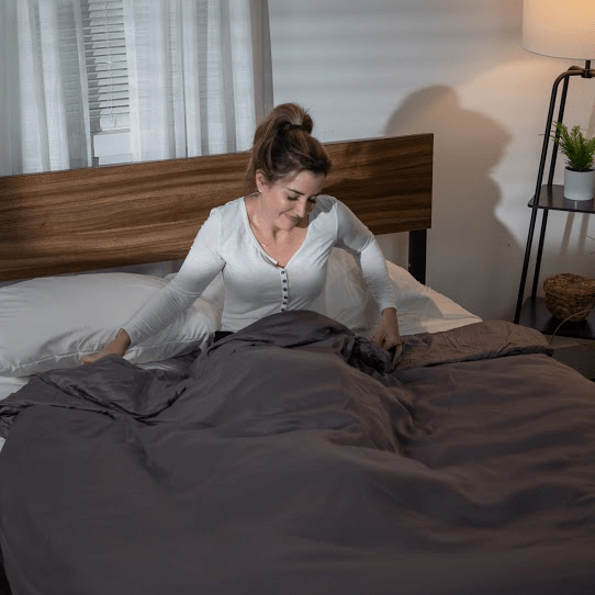 Smiling woman sitting on the bed with a weighted blanket