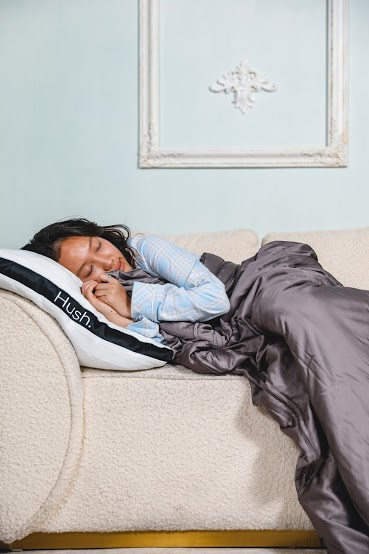 too hot to sleep: Woman sleeping on the couch while hugging a weighted blanket