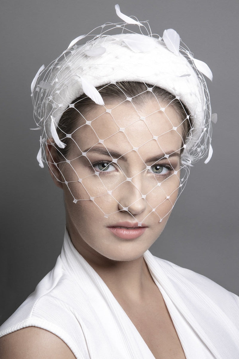 Unique felt headpiece with veil and feather details.  Wear this striking headpiece as an alternative to a birdcage veil.  The veil can easily be tucked under the headband should you wish to wear it without the veil.