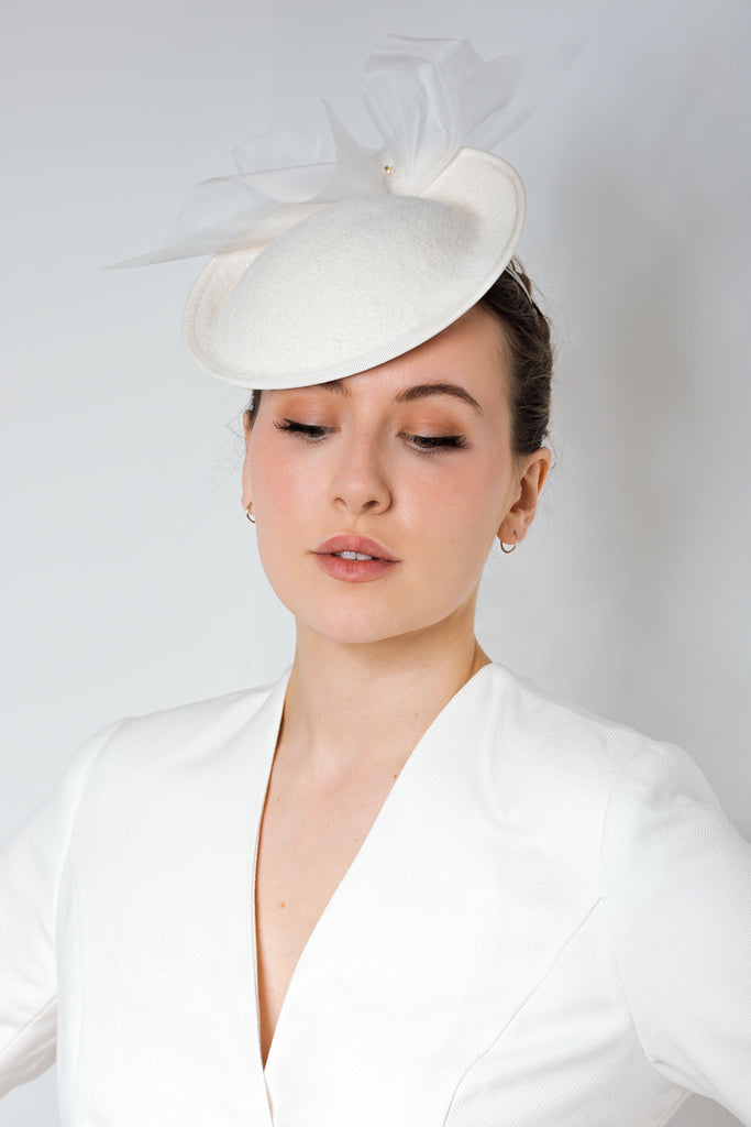 Our Soraya hat is an elegant wedding saucer hat, The design is hand-formed into this unique shape and finished with a fine crinoline flourish and Swarovski pearl detail.