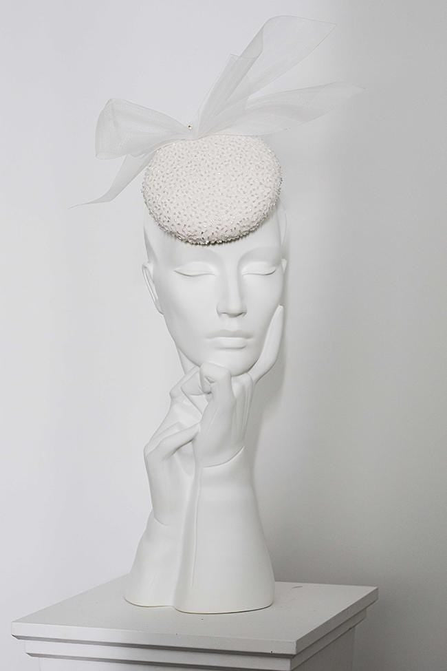 Our Meira wedding hat is created with a beautiful beaded organza over silk.  The hat is finished with a crin flourish and small pearl detail.  The wedding hat secures with a millinery headband which can be dyed to compliment your hair colour, please enter your hair colour when ordering. One Size.