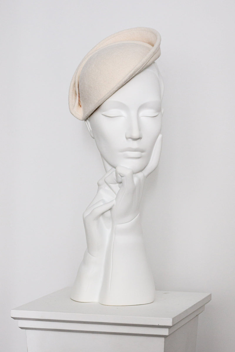 Our Neyva wedding is an elegantly hand formed percher hat made from velour felt. Sculpted by hand, the edge is then wired and finished with two small rose gold beads. A small detachable birdcage veil is also available, see our Morven hat for information.  The angle of this hat is flattering with many face shapes, please contact us if you would like advice on suitability.