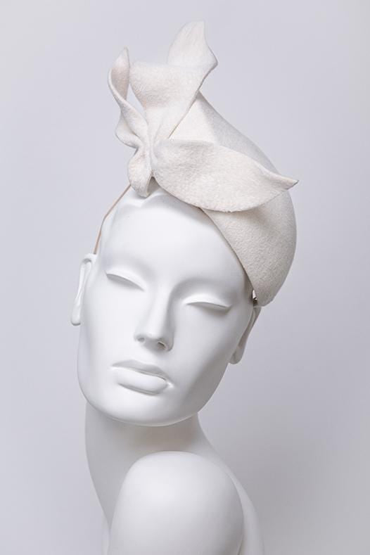 Elegant wedding hat with felt trim.  A striking wedding percher hat created in off white felt and finished with a large felt detail, giving height and movement to the design.  Hat is made velour felt. This headpiece is handmade, slight variations may occur.  Lining is made from satin. This hat attaches with elastic.