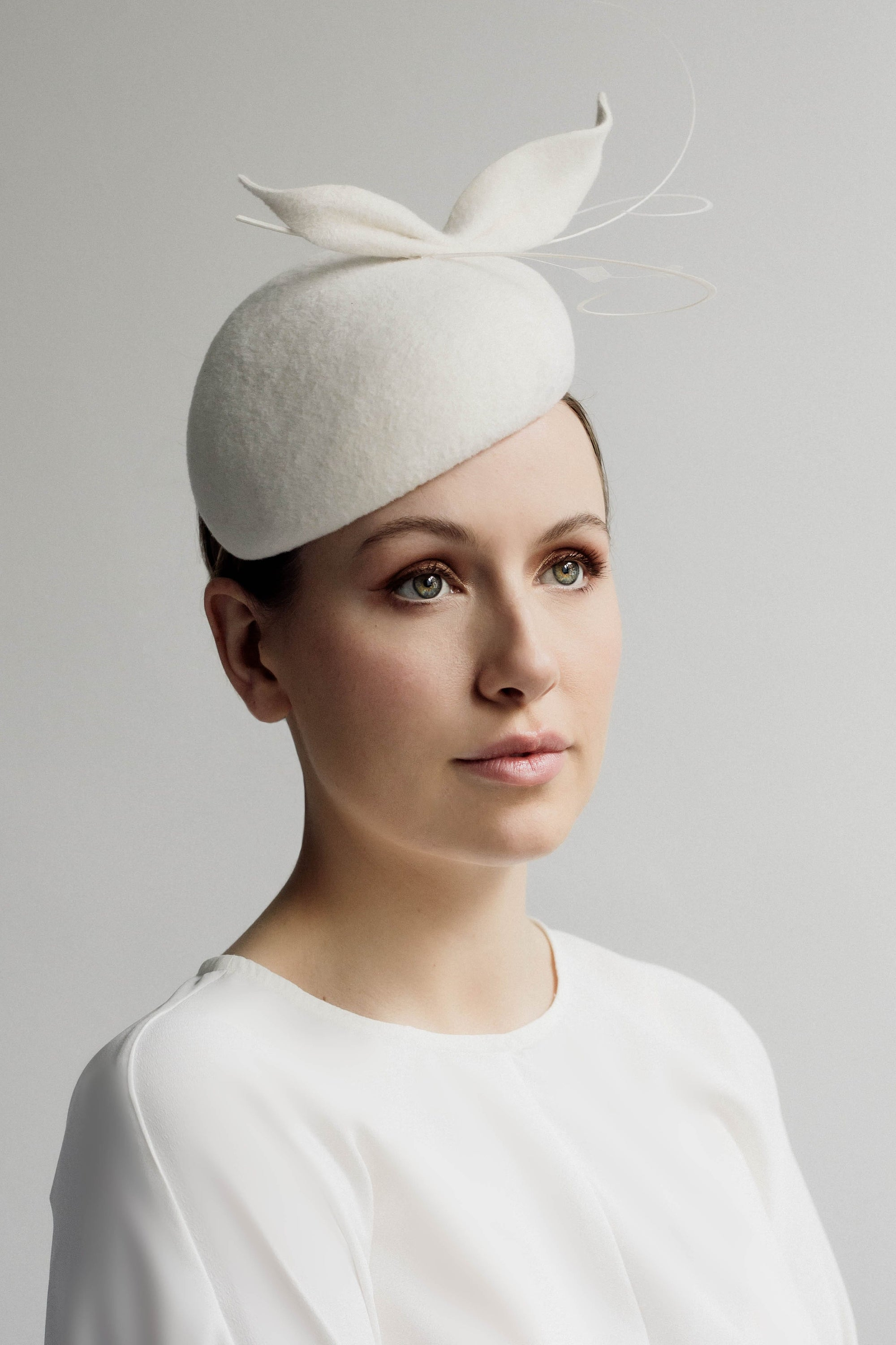 Sasha is a flattering wedding percher hat with felt and feather details.  Our elegant Sasha wedding cocktail hat is created in off white velour felt and finished with a felt detail and complimentary feathers.  This wedding hat is made using velour felt. This headpiece is handmade, slight variations may occur.  Lining is made from satin. This hat attaches with elastic & metal comb or headband. One size Made to order Can be made in other colours on shade chart.