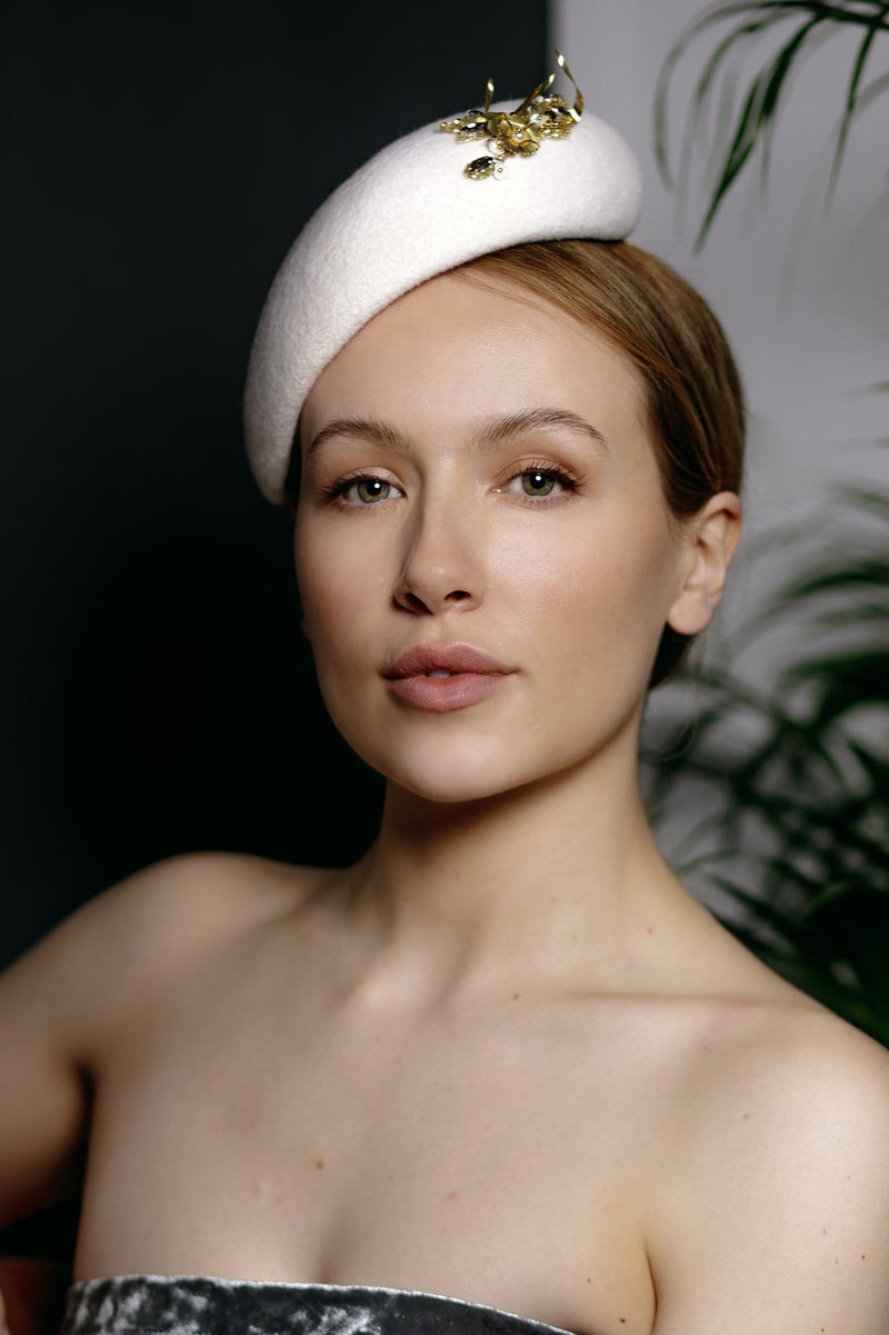 Our Lila design a simple yet elegant wedding hat, made in off-white colour velour felt and finished with a small gold hand beaded detail.  The beads are made up of flower beads, curled sequins and diamanté. The details can also be made in silver.