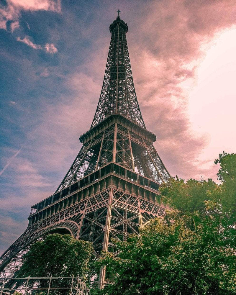 This is a beautiful photo of Eiffel tower with green trees  in a bright cloudy day