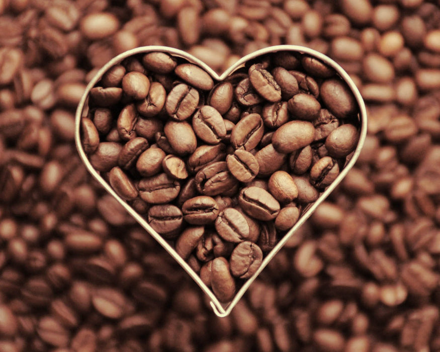 This is a photo (close up shot) of coffee beans in heart shape outline