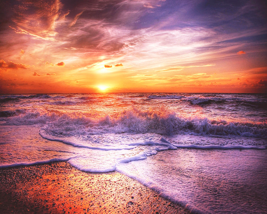 This is a photo of a sunrise at the beach with a pastel colored skies.