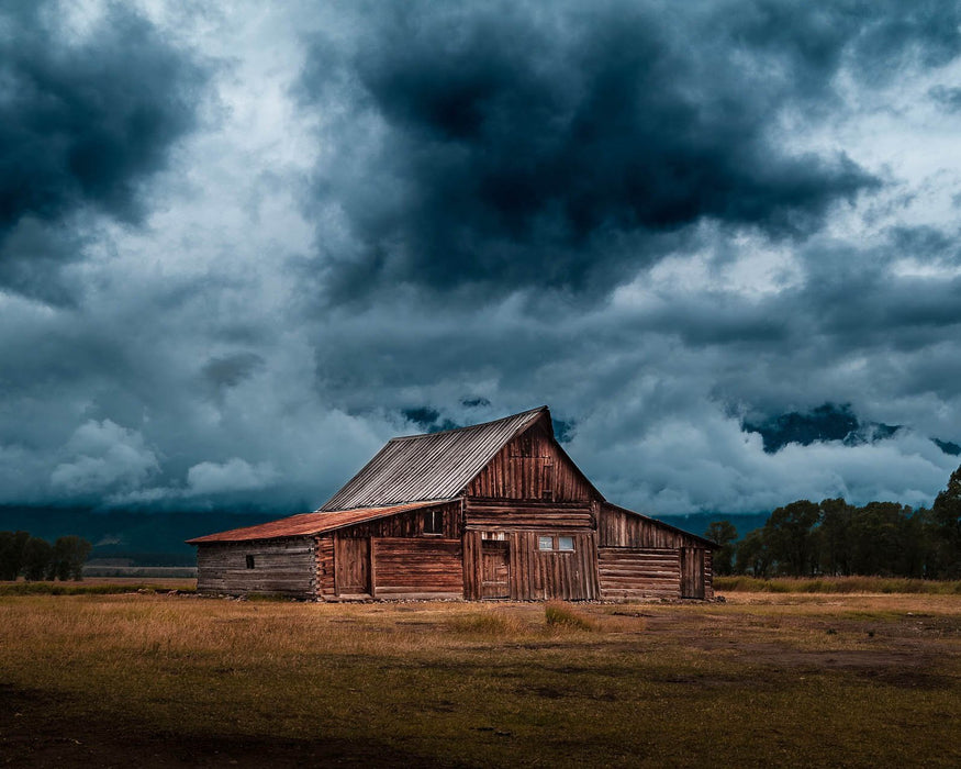 This is a photo of brown barn in the green fields over the stormy clouds.