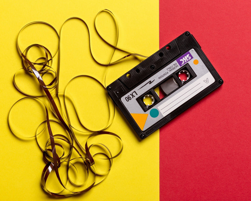 This is a photo of a cassette tape in vintage yellow and red background.